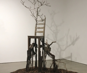 Deception • Full Right View • Mixed Media Black Walnut Branch, Chair, Acrylic Paint, Sumac Roots and Faux Roots, Black Walnuts, Potting Soil 112 inches x 70 inches x 60 inches (285 cm x 178 cm x 122 cm)