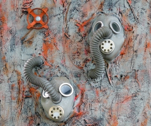 Only Two • Mixed Media, Tar, Plaster Wrap and Acrylic on Panel with World War I Gas Masks and Faucet Valve, Sonic (Singing) Interactive: Speakers mounted at hose end with sound exiting mask's speaker, Electronics mounted on back, 24 X 18 inches (61 x 46 cm)