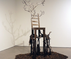 Deception • Full Left View • Mixed Media Black Walnut Branch, Chair, Acrylic Paint, Sumac Roots and Faux Roots, Black Walnuts, Potting Soil 112 inches x 70 inches x 60 inches (285 cm x 178 cm x 122 cm)
